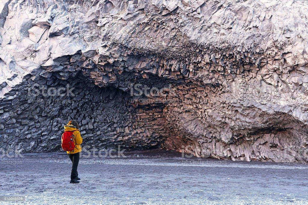 Hiker Admiring Basalt Columns on Vik Beach in Iceland stock photo