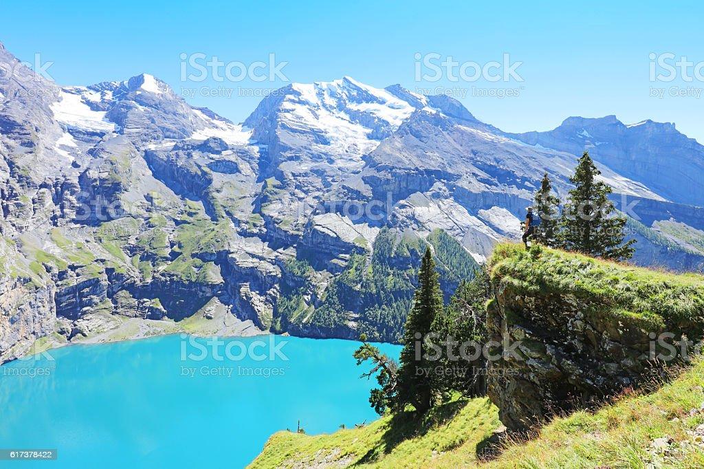 Hiker Admiring Oeschinen Lake from Heuberg Lookout in Switzerland stock photo