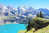 Hiker Admiring Oeschinen Lake from Heuberg Lookout in Switzerland