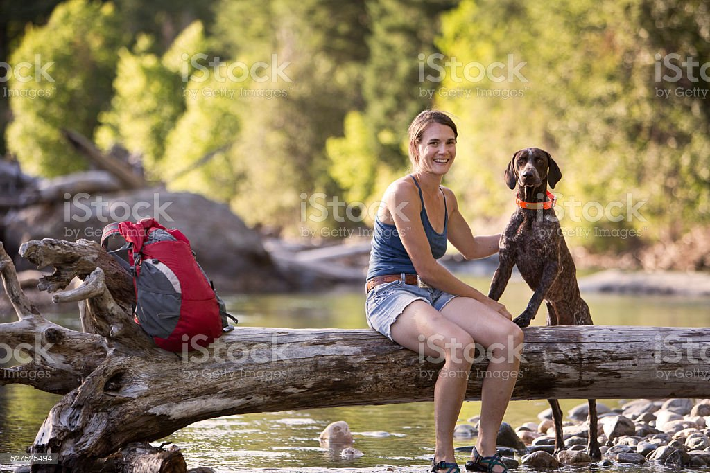 Hiker and Dog Sitting by a Stream in The Mountains. stock photo