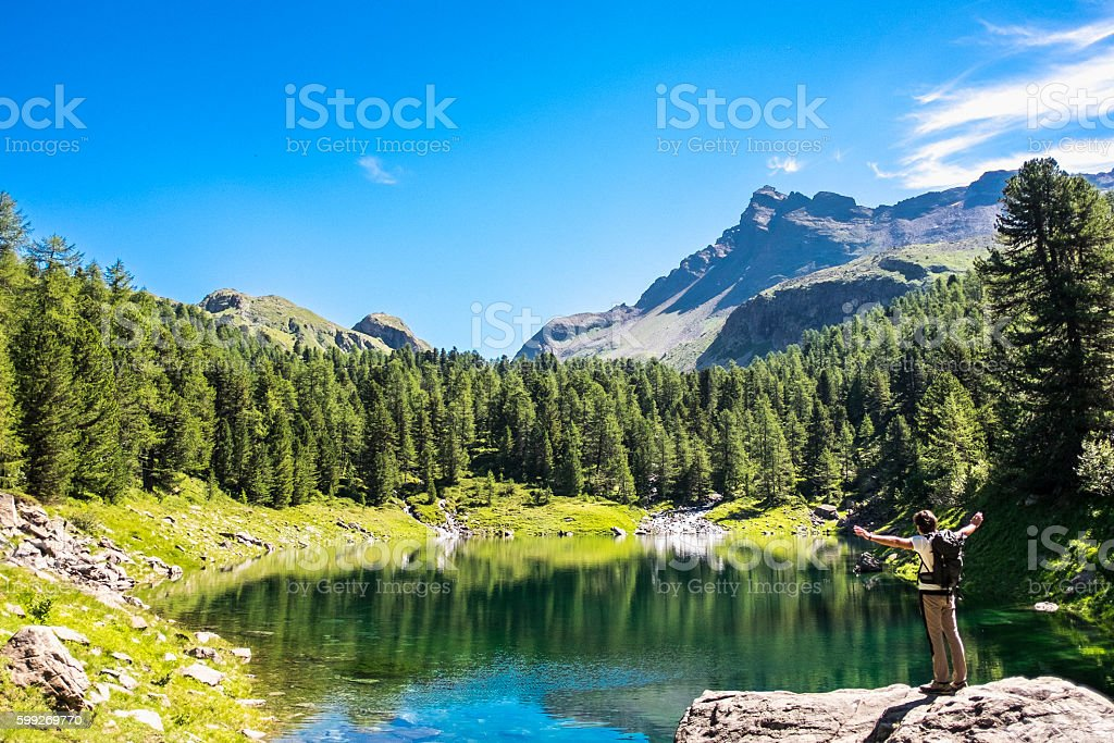 Hiker and mountain lake in the background stock photo