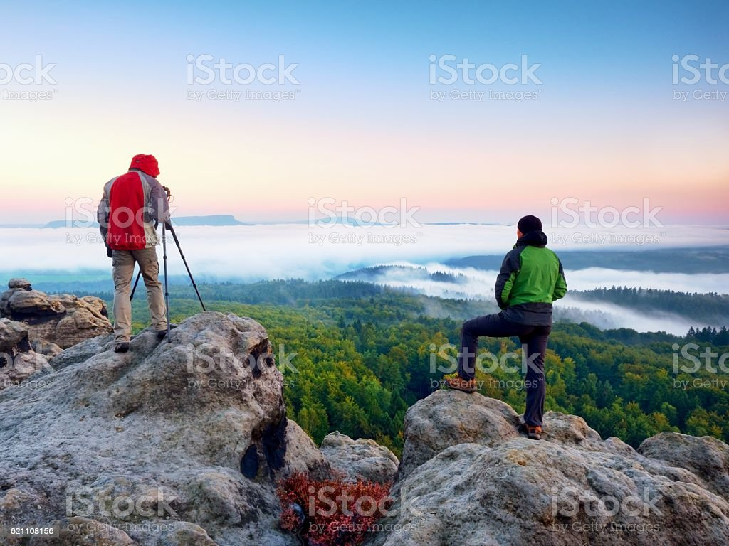 Hiker and photographer  with tripod on cliff . Autumn landscape, stock photo