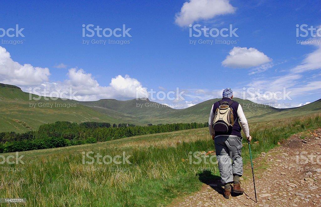 Hiker approaching hills stock photo