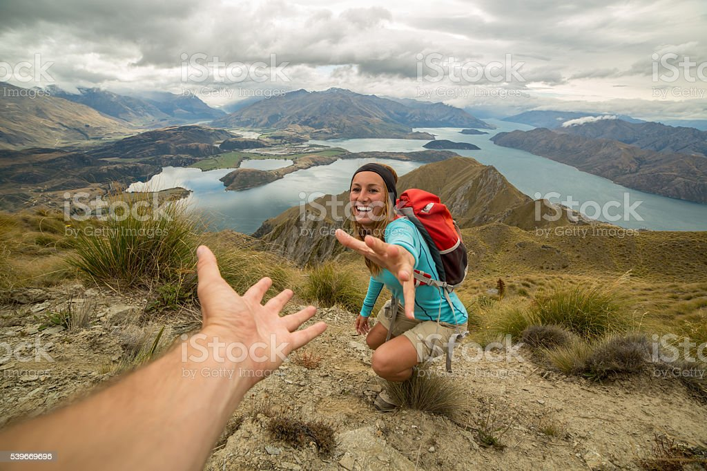 Hiker assists teammate on mountain top stock photo