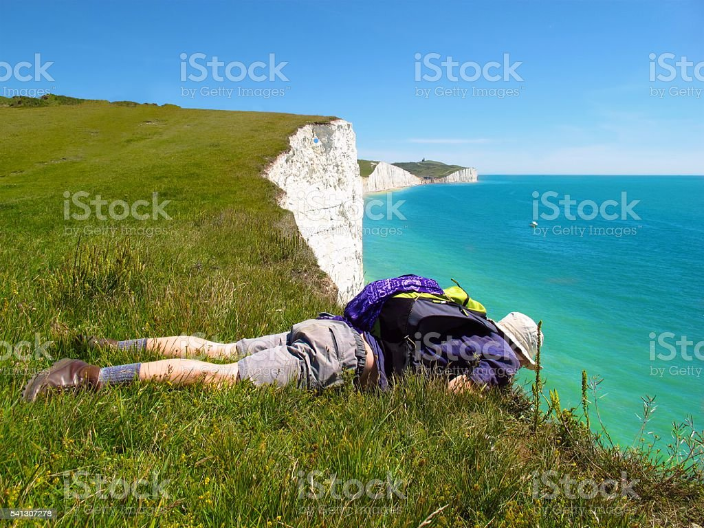 Hiker at edge of white cliffs Seven Sisters Eastbourne England stock photo