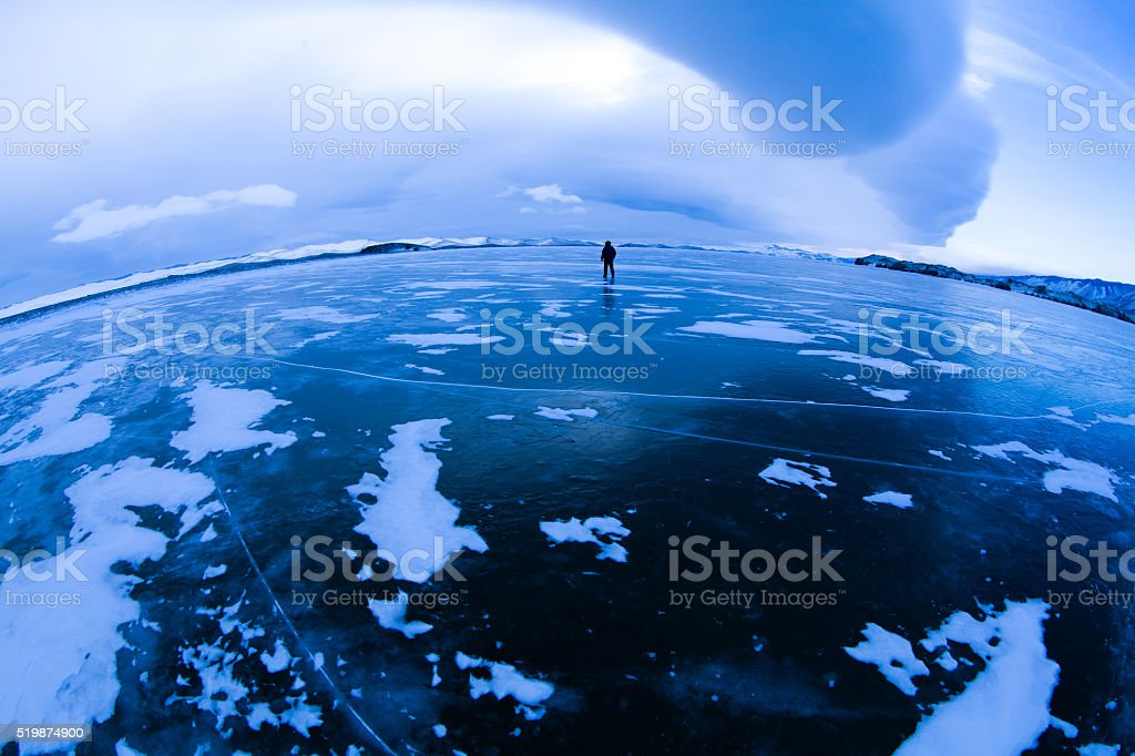 Hiker at frozen lake stock photo