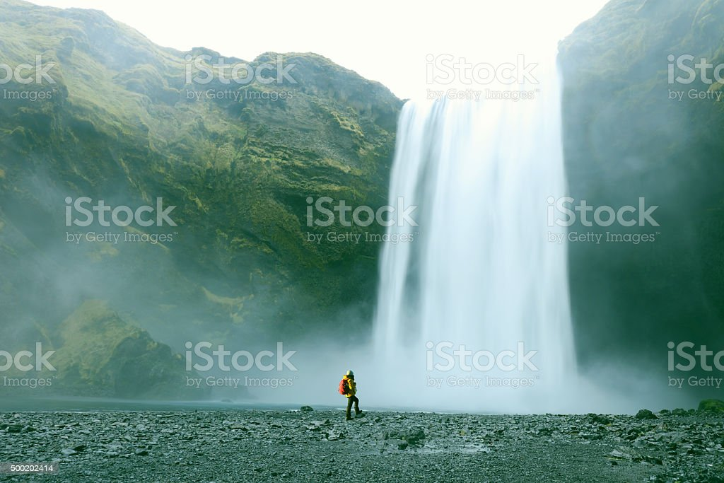 Hiker at Majestic Skogafoss Waterfall in Iceland stock photo