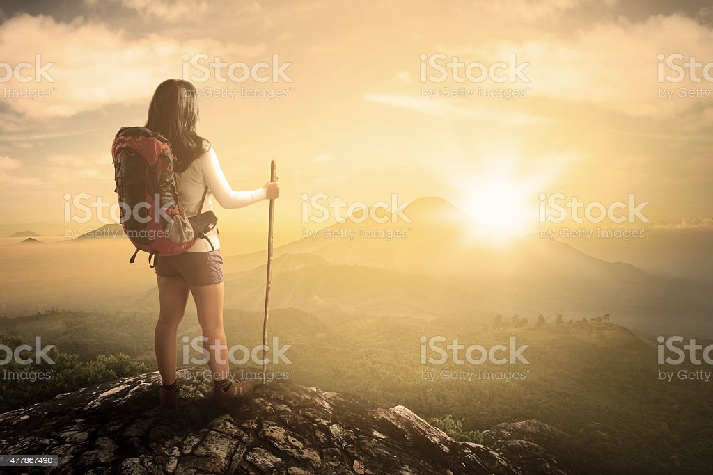 Hiker at mountain peak looking the valley view stock photo