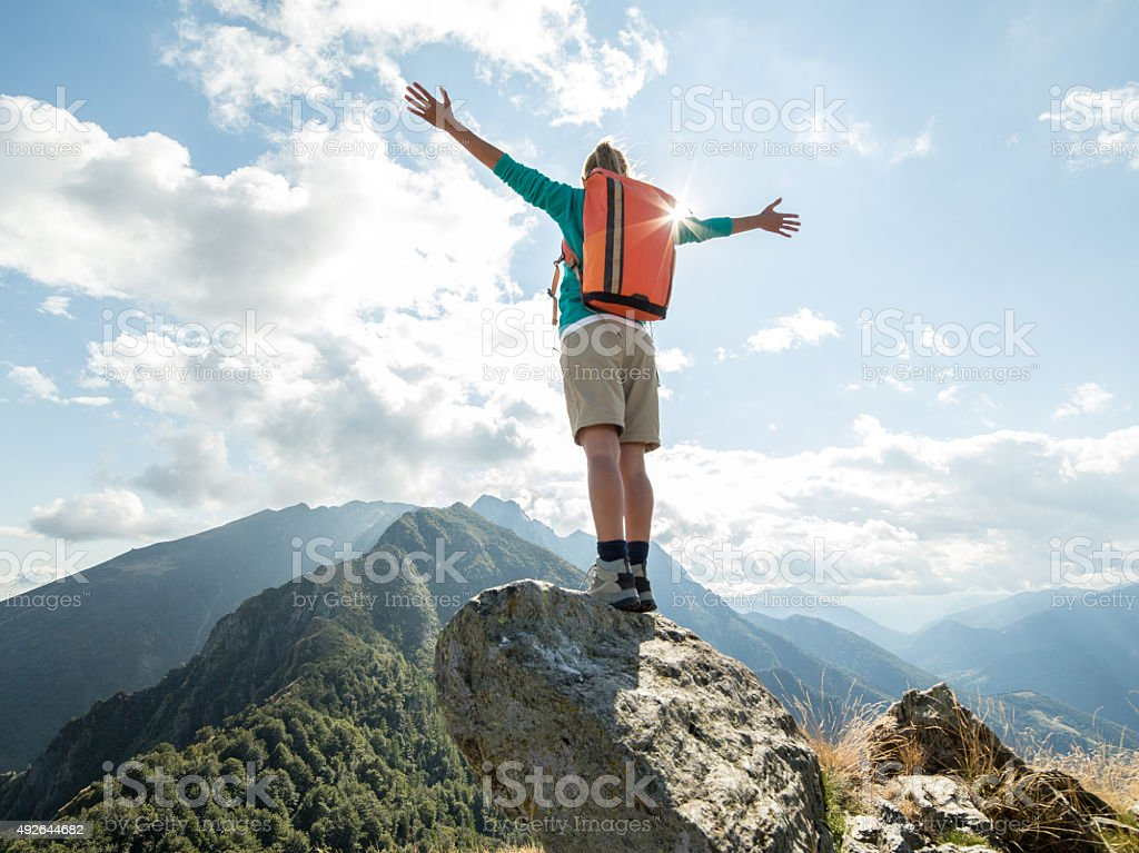 Hiker at mountain top arms outstretched stock photo