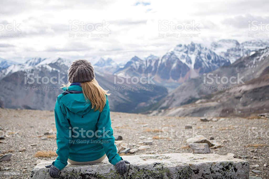 Hiker at mountain top enjoying landscape stock photo