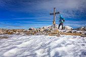 Hiker at summit cross on Mount Hohes Brett  - Alps