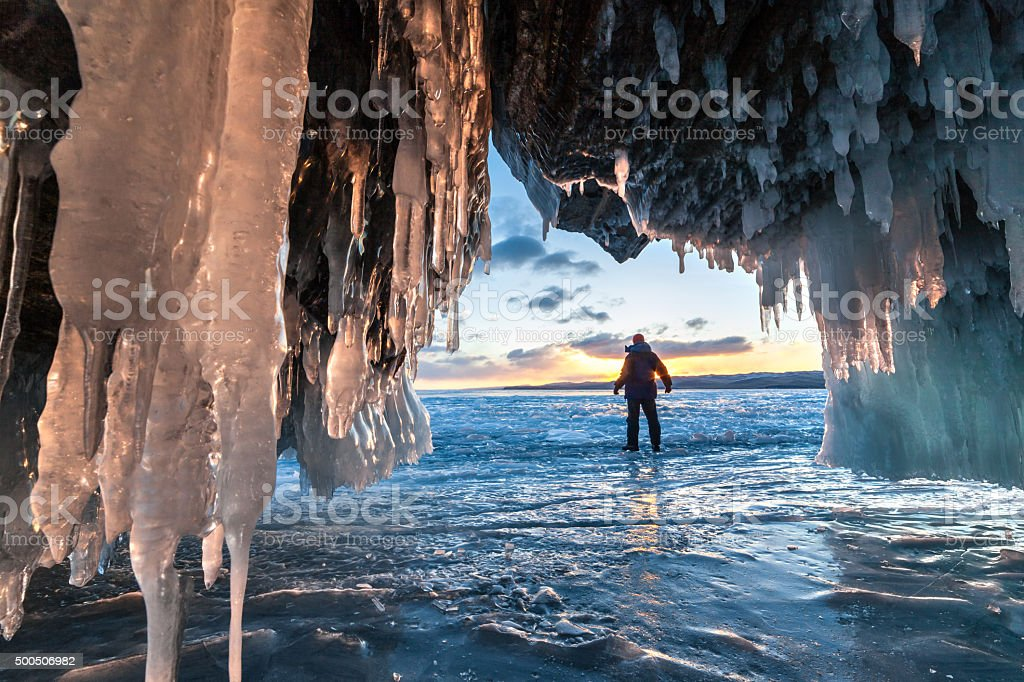 Hiker at the ice cave and across sunrise. stock photo