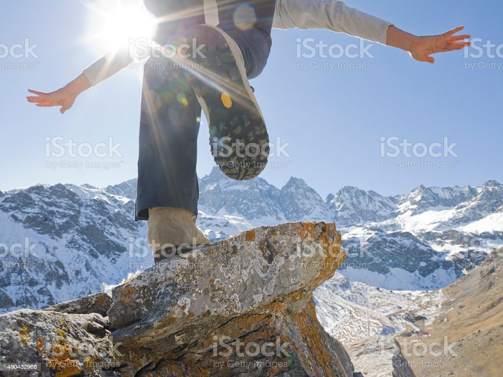 Hiker balances on rock summit above mountains stock photo