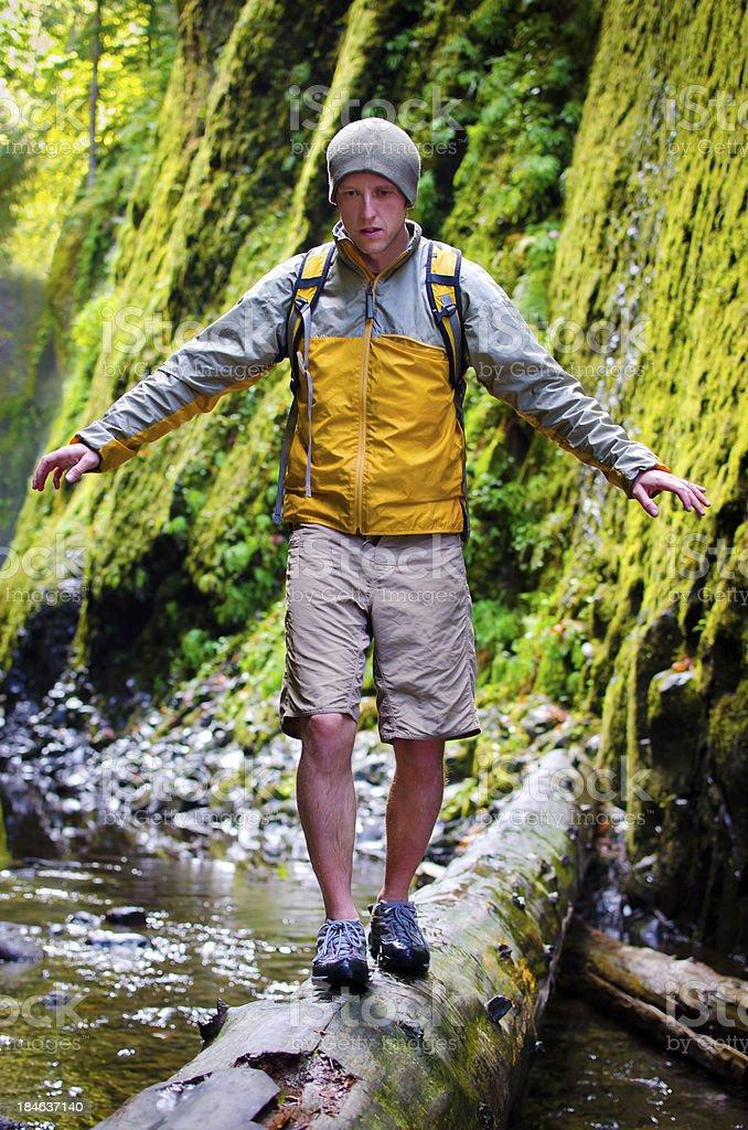 Hiker balancing on log stock photo