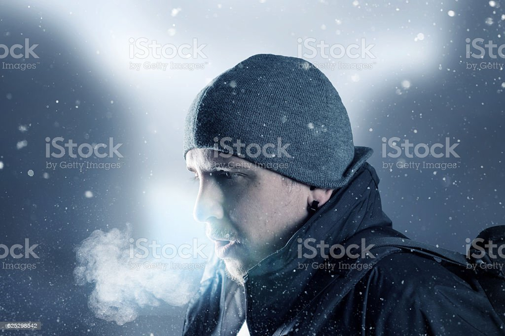 hiker breathe out in front of blurred mountain landscape stock photo