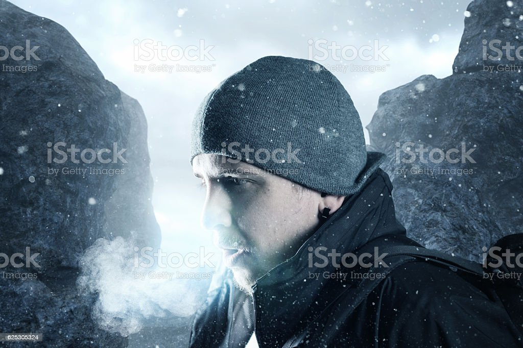hiker breathe out in front of mountain landscape stock photo