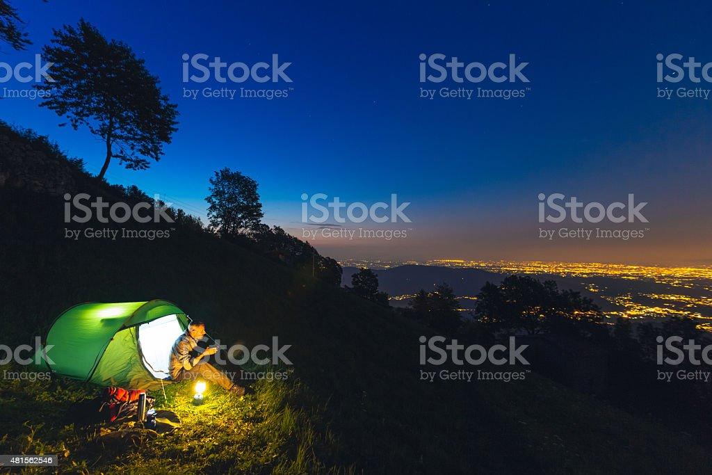 Hiker camping at night stock photo