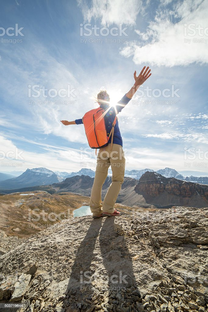 Hiker celebrating on mountain top stock photo