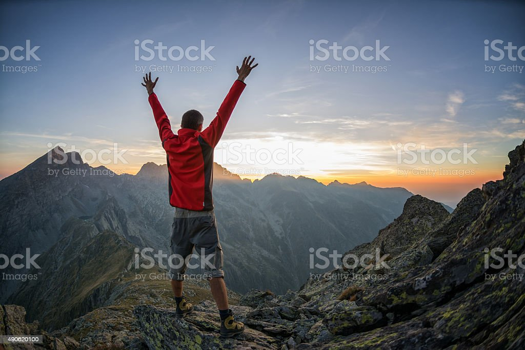Hiker celebrating success in the sunset stock photo