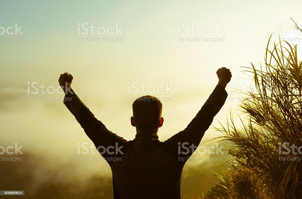 Hiker celebrating success on the top of mountain. stock photo