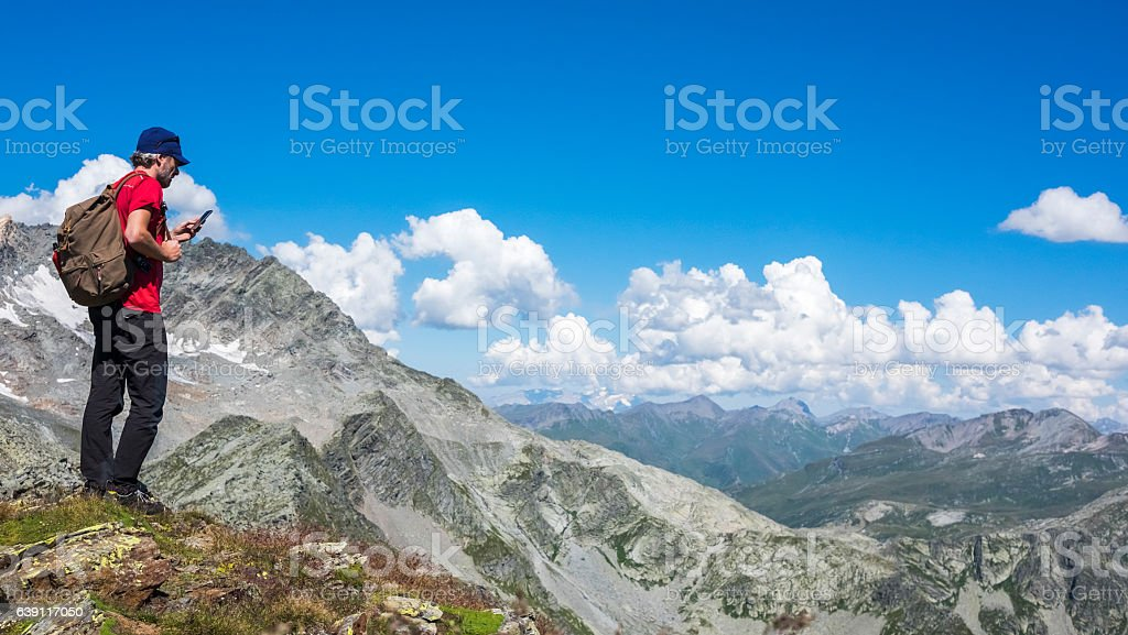 Hiker checking device on mountain ranges stock photo