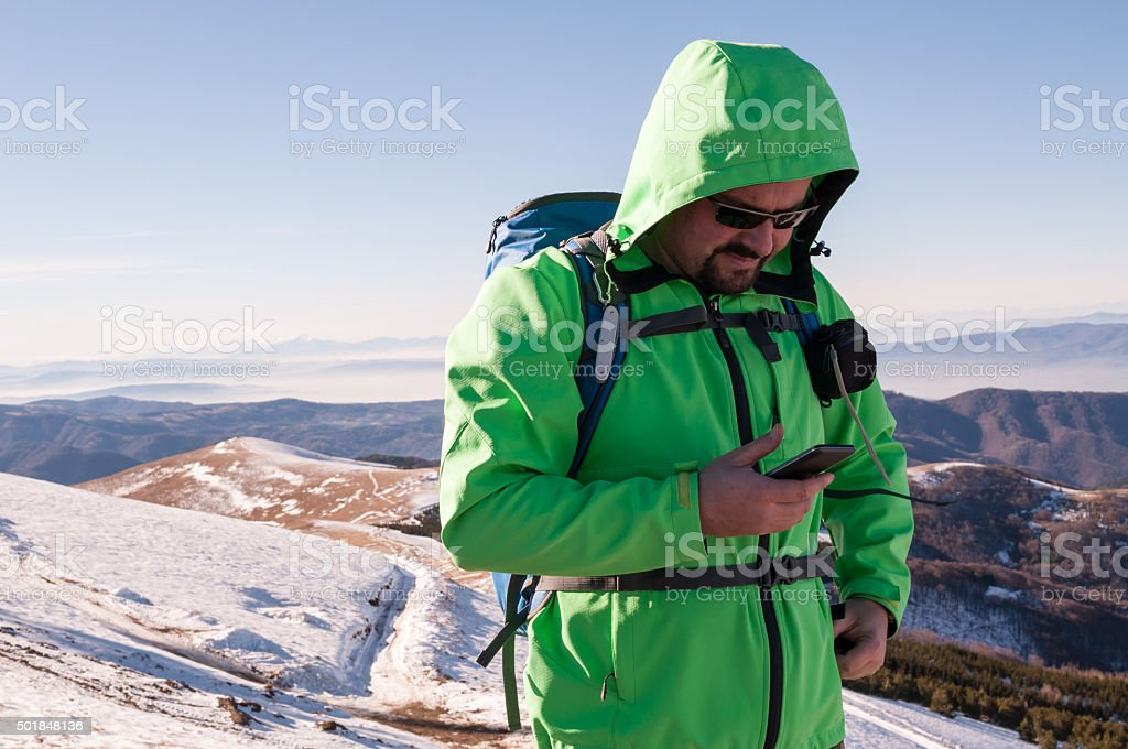 Hiker checking his smartphone stock photo