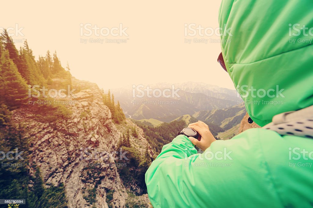hiker checking the altimeter on sports watch at mountain peak stock photo