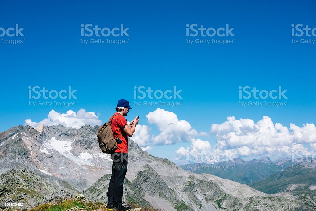 Hiker checks the smartphone on top of the mountain stock photo