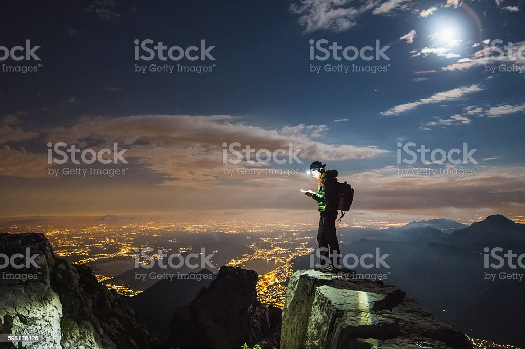 Hiker checks your device on top on the mount stock photo