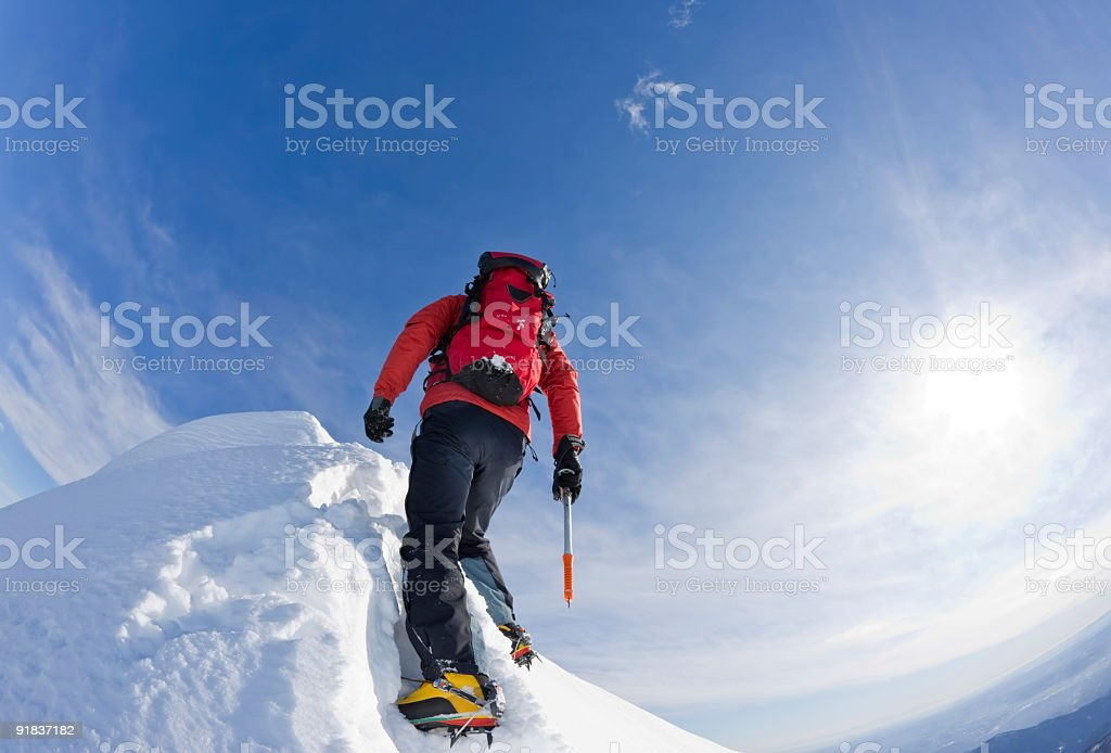 Hiker climbing up on a snowy mountain with sky background stock photo