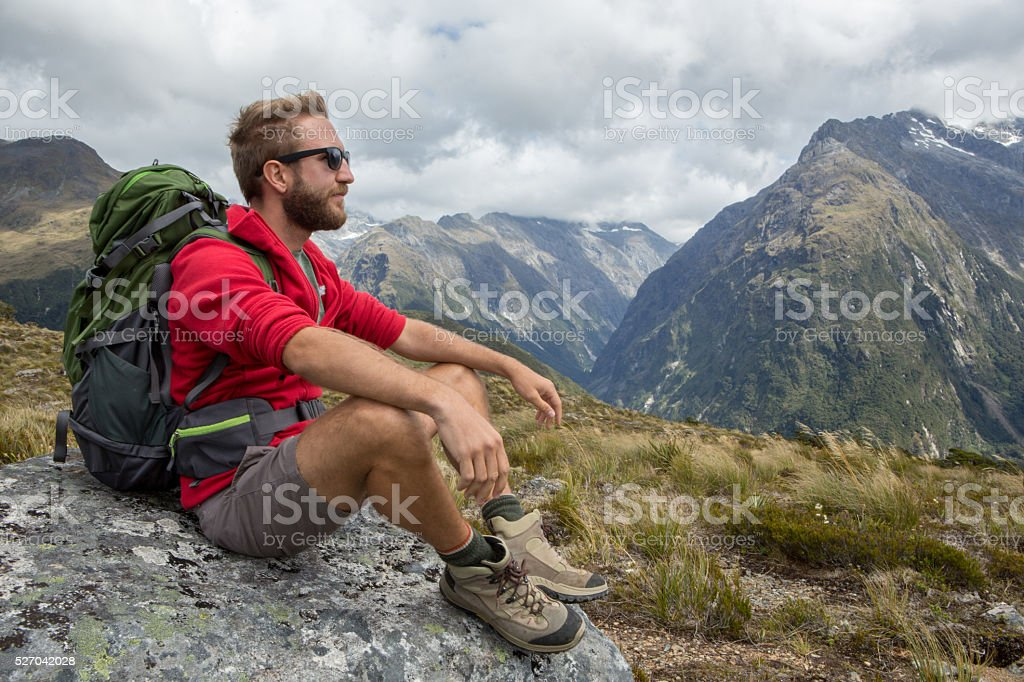 Hiker contemplating nature from mountain top stock photo
