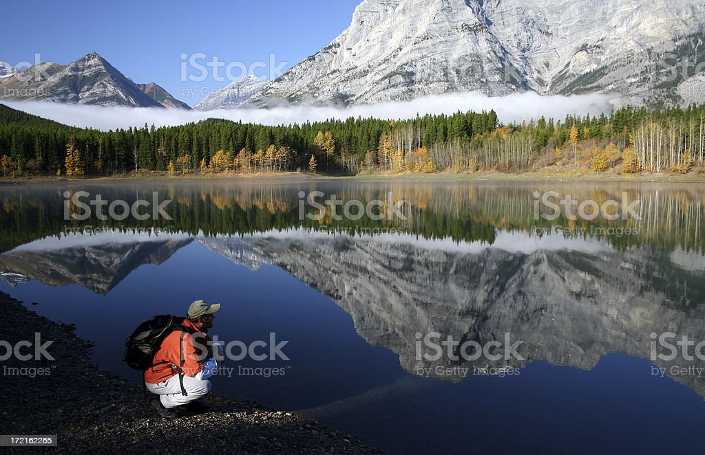 hiker contemplating the serenity of a mountain lake royalty-free stock photo