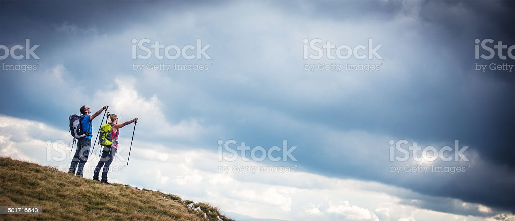 Hiker couple pointing at the cloudy sky stock photo