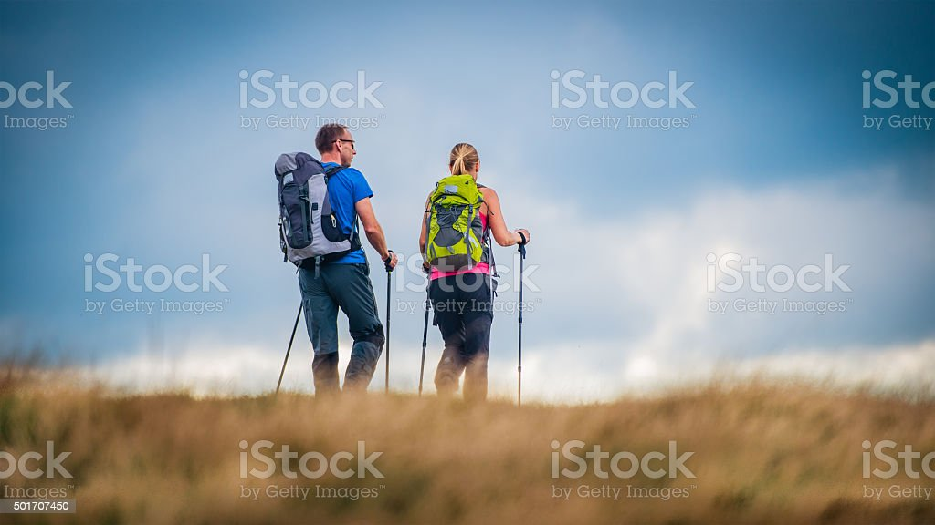 Hiker couple walking across a meadow on a plateau stock photo