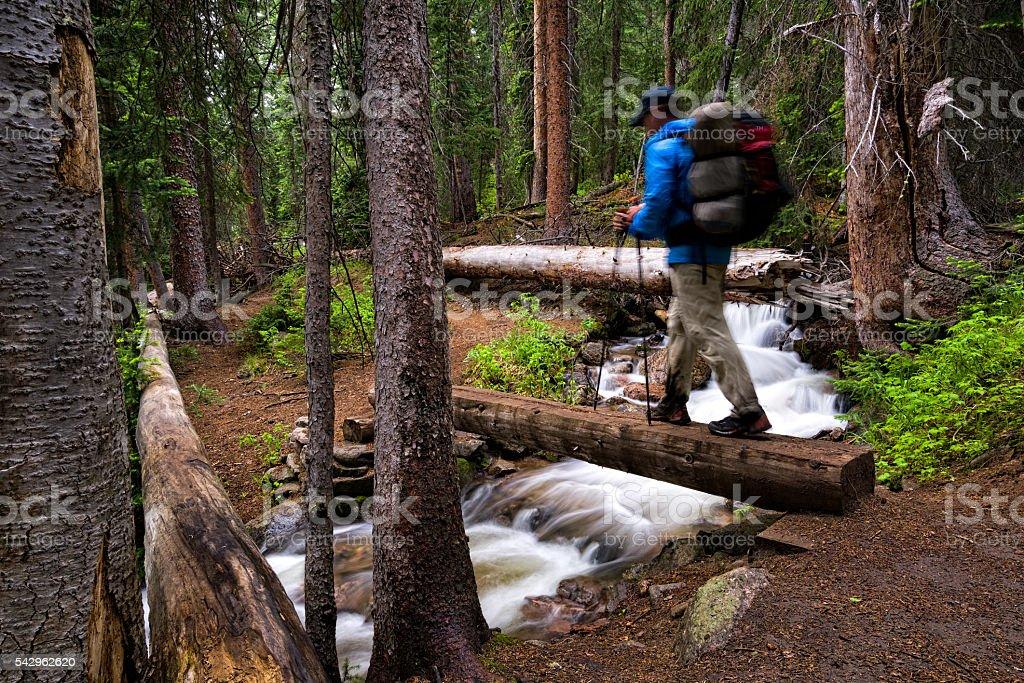Hiker Crosses Bridge Over Mountain Creek stock photo