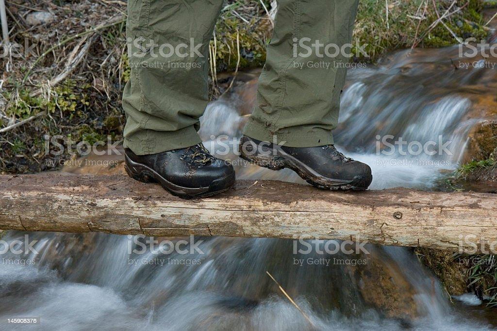 Hiker crossing foot bridge stock photo