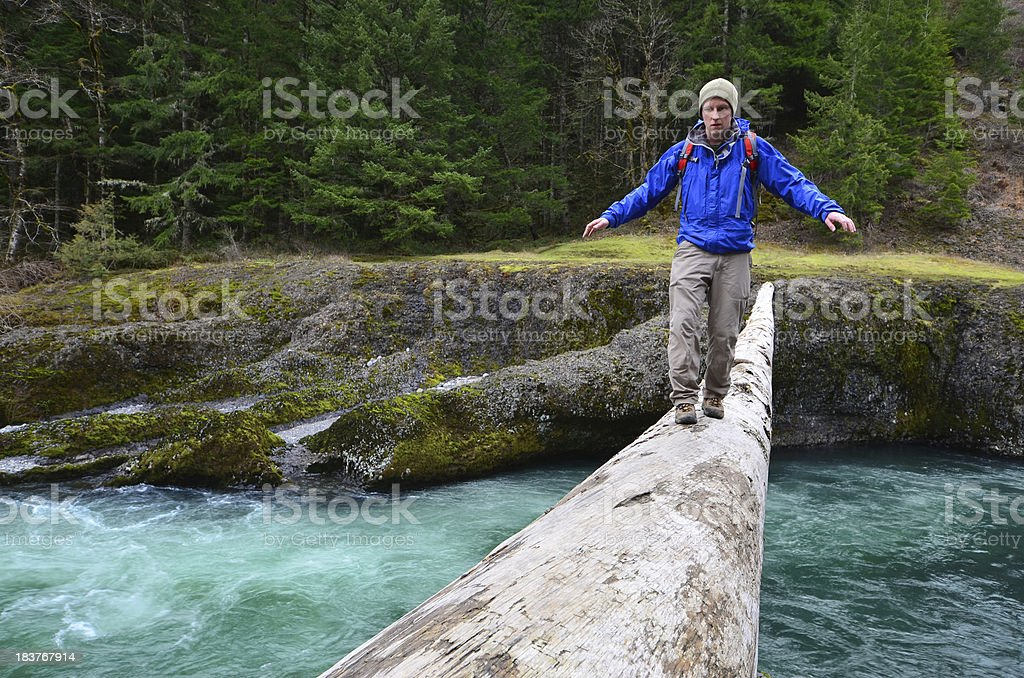 Hiker crossing log stock photo