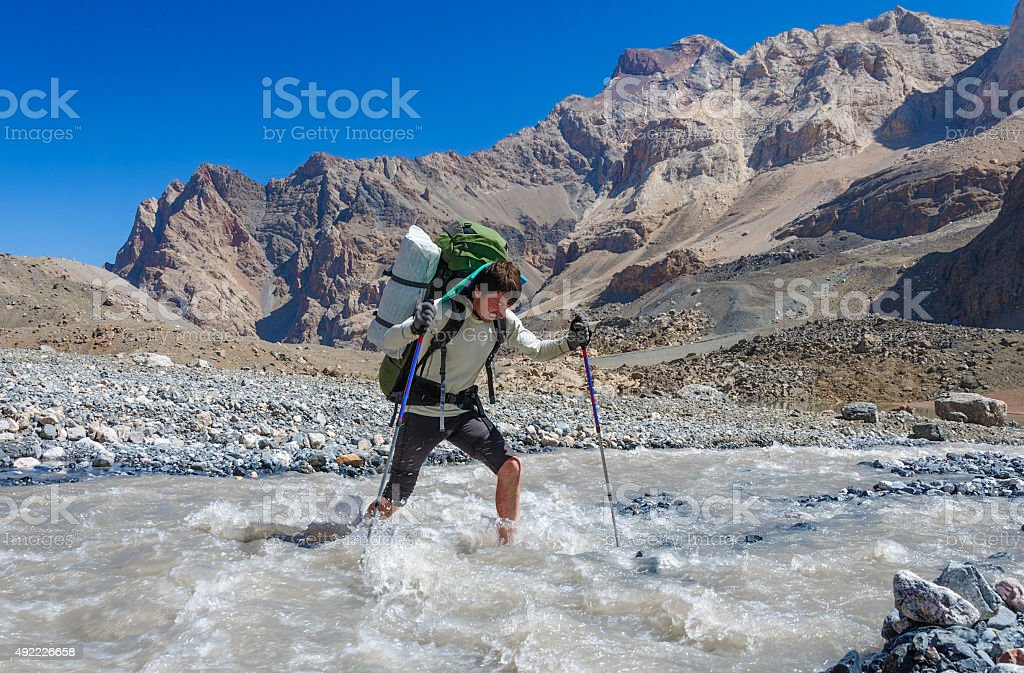 Hiker crossing mountain river stock photo