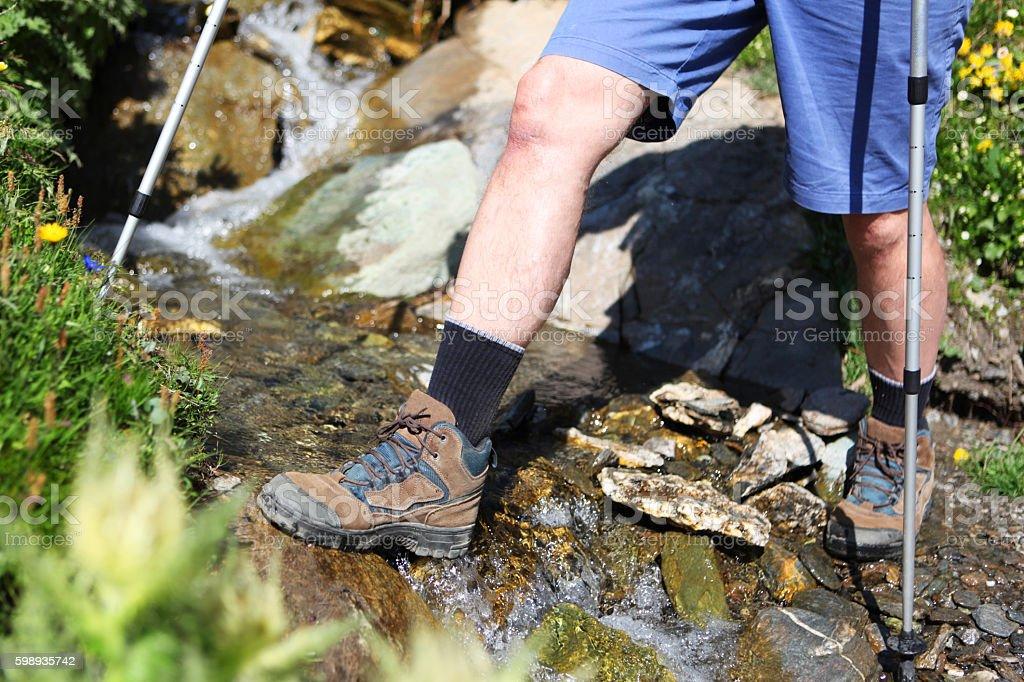 Hiker Crossing Mountain Stream in Swiss Alps stock photo