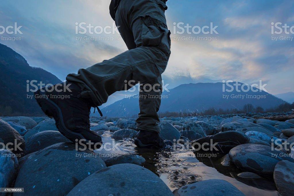 Hiker crossing river stock photo