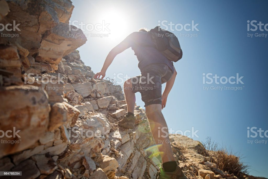 Hiker crossing rocky terrain stock photo