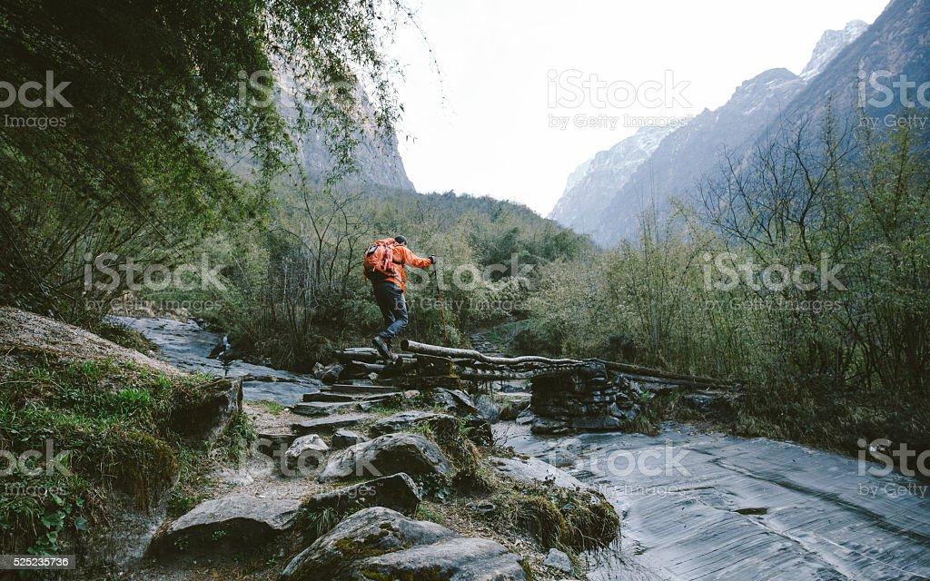 Hiker crossing the bridge stock photo