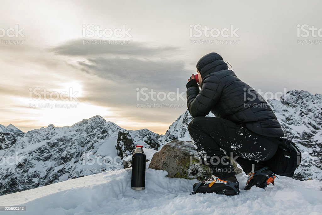 Hiker drink hot tea in the winter in the mountains. stock photo