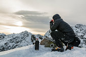 Hiker drink hot tea in the winter in the mountains.