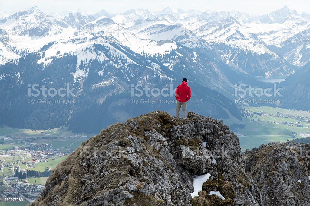 hiker enjoying the view from aggenstein stock photo