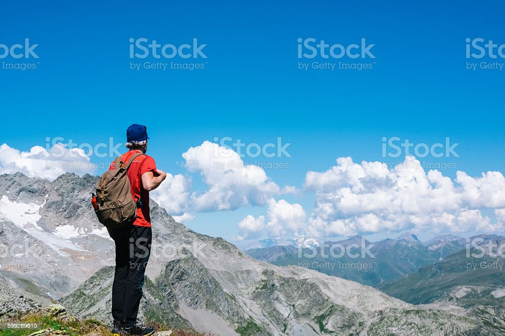 Hiker enjoying view of mountain ranges from the top peak stock photo