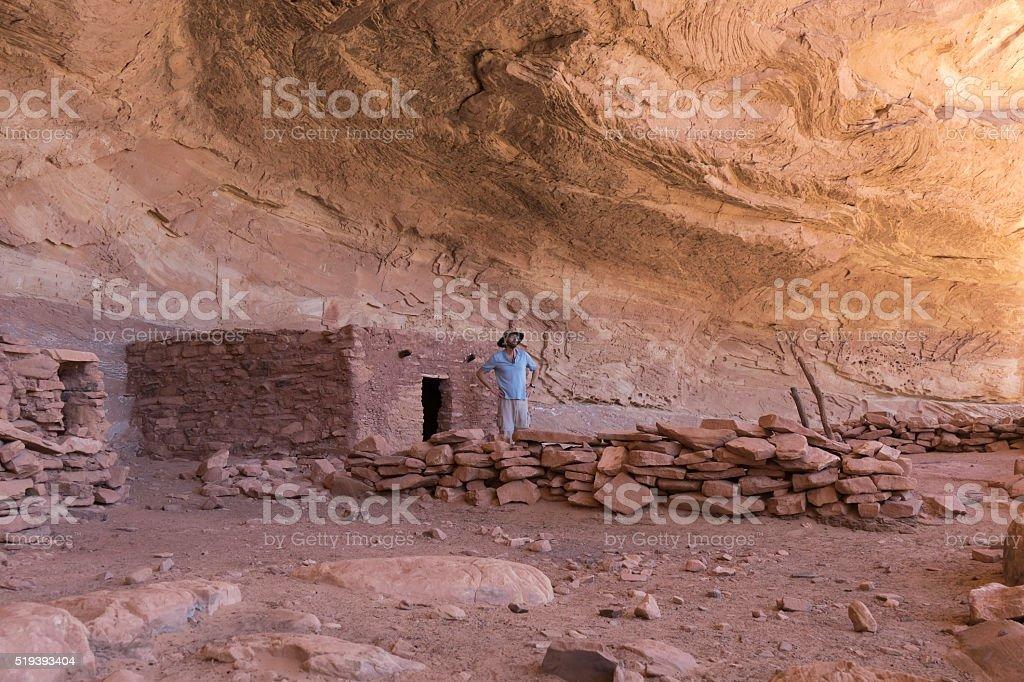 Hiker enjoys exploring Cedar Mesa Pueblo ruins Utah stock photo