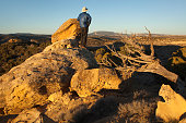 Hiker enjoys sunset over Colorado's red rock Cathedral Bluffs