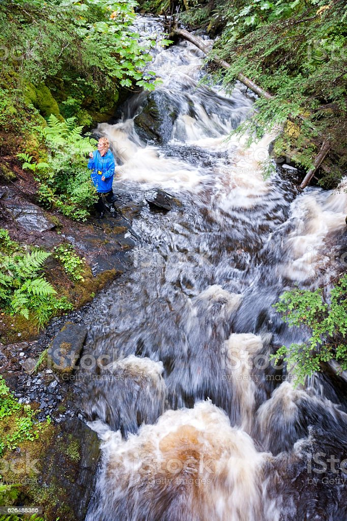 Hiker explores a waterfall in Juneau forest stock photo