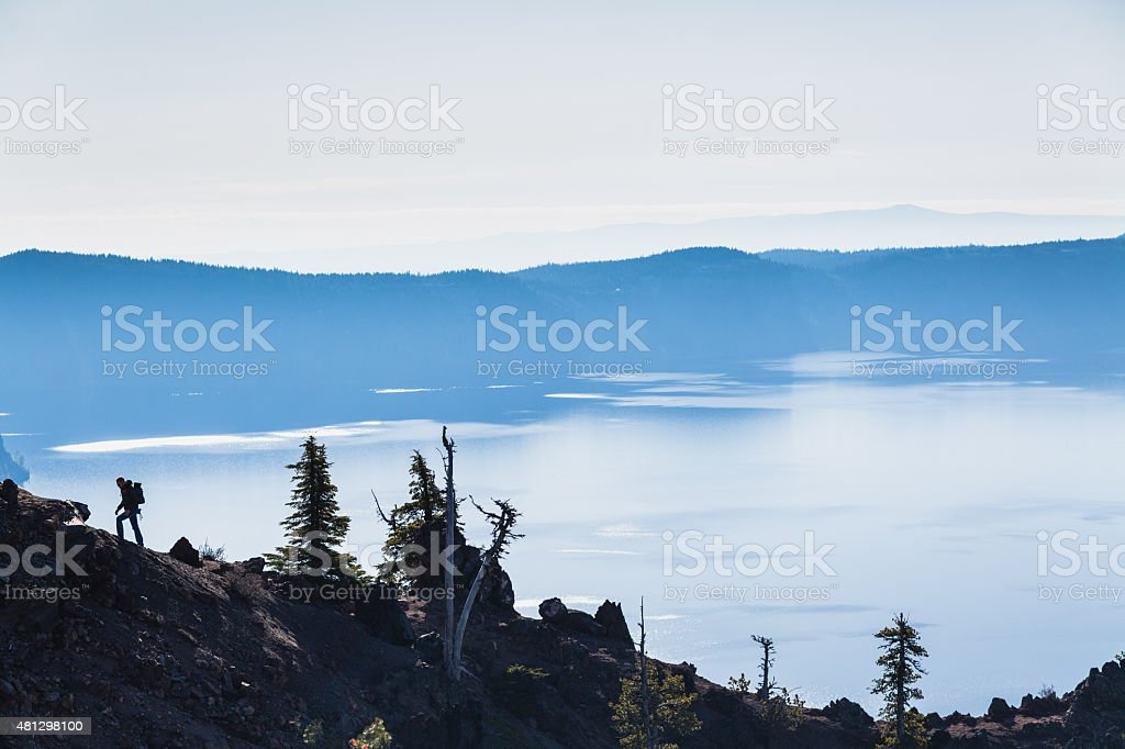 Hiker explores the Crater Lake in Oregon. stock photo